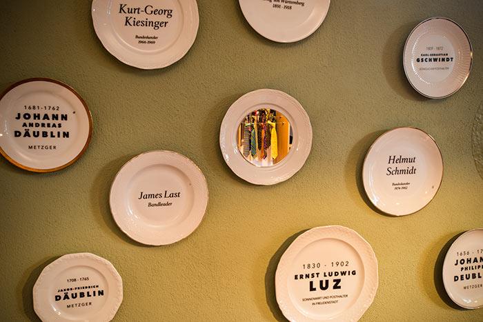 Sammlung dekorativer Teller mit Beschriftung vergangener Wirte.