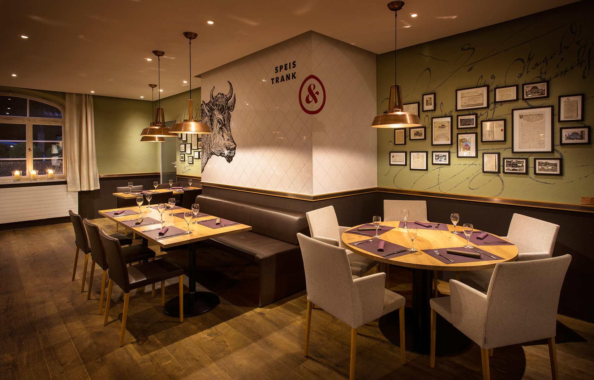 Innenraum des Restaurantteils mit gedeckten Tischen und neu gestalteten Wänden.