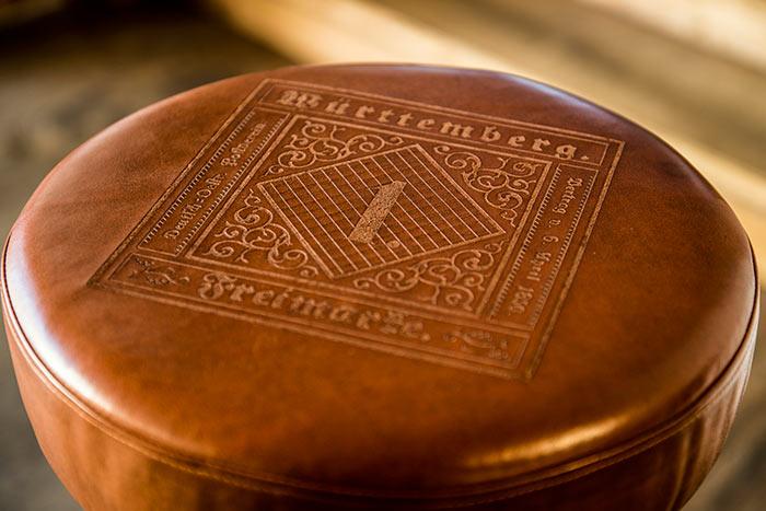 Lederbezogener Hocker mit dekorativ eingraviertem Emblem.