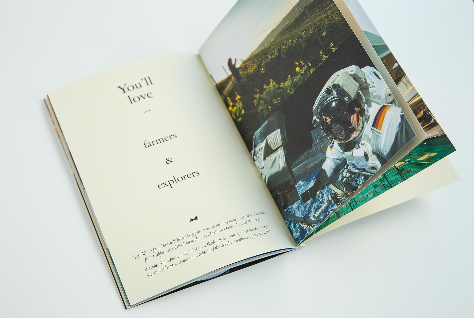 Aufgeschlagene Broschüre. Auf einer Seite ist die Headline 'You'll love ... farmers & explorers' zu lesen. Auf der anderen Seite sieht man das Bild eines Mannes von Dautel Winery auf einem Weinberg bei der Arbeit. Darunter das Bild vom Astronauten und ISS-Captain Alexander Gerst im Weltall.