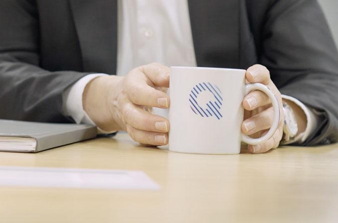 Mitarbeiter hält Tasse bedruckt mit Bosch Quality Principles Logo