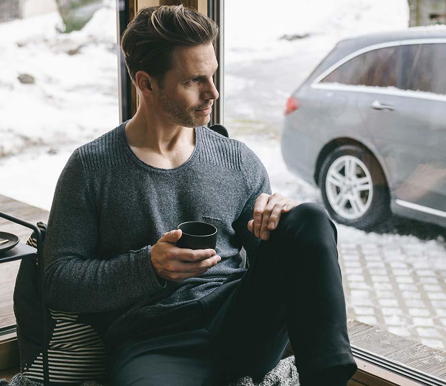 Mann sitzt am Fenster und hat eine Tasse in der Hnad