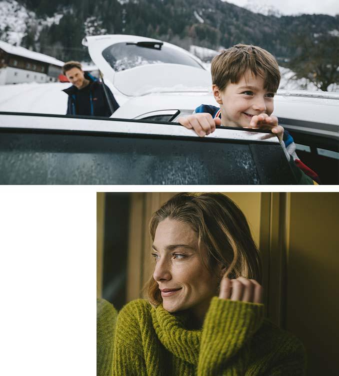 Mann mit seinem Kind am Auto und eine Frau sieht aus dem Fenster