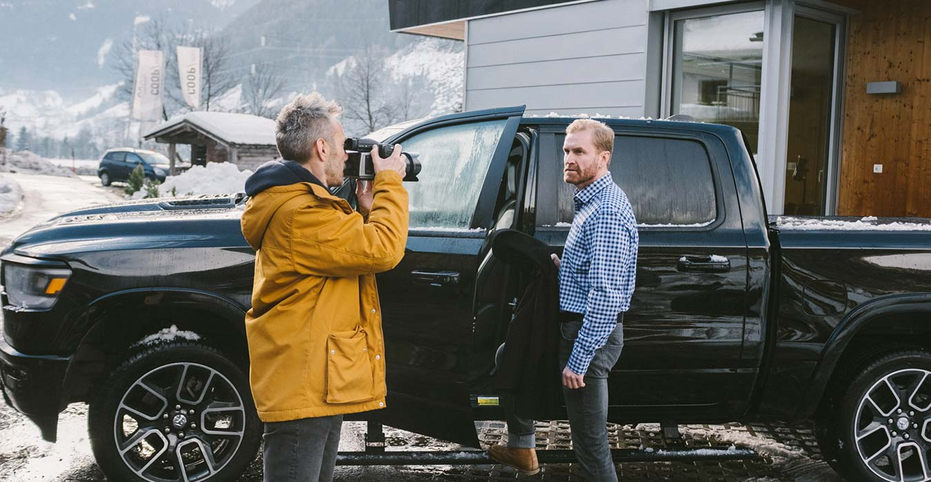 Fotograf fotografiert einen Mann am Auto