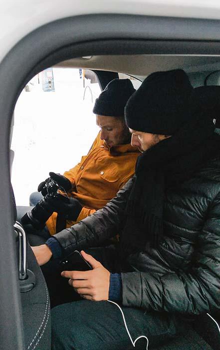 Zwei Männer sitzen im Auto und schauen sich Bilder im Kamera-Display an