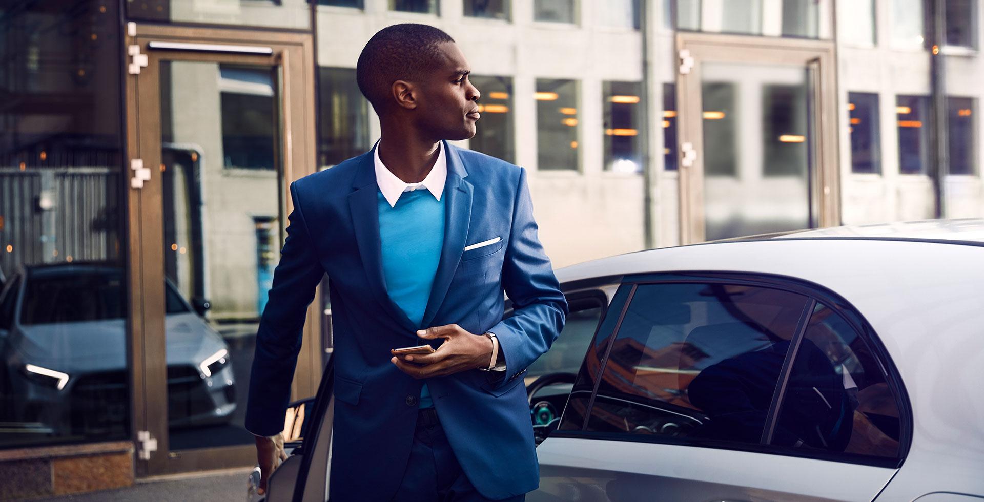 Foto aus dem Bilderpool für Mercedes-Benz Global Service & Parts. Junger Mann mit Smartphone in der Hand steigt aus einem Mercedes, dessen Front sich in einer gegenüberliegenden Glasscheibe spiegelt.