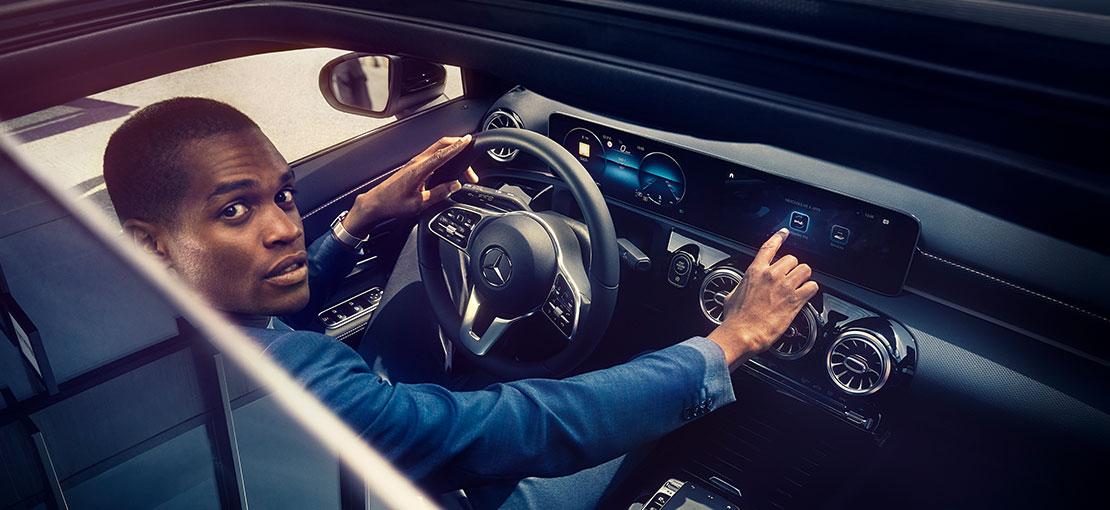 Blick durch das Schiebedach einer Mercedes A-Klasse: Junger Mann sitzt am Steuer und bedient das MBUX Multimedia-System auf dem Widescreen.