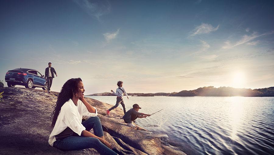 Junge Familie an einem Ufer. Die Kinder spielen am Wasser, der Vater läuft vom im Hintergrund geparkten Mercedes auf sie zu.