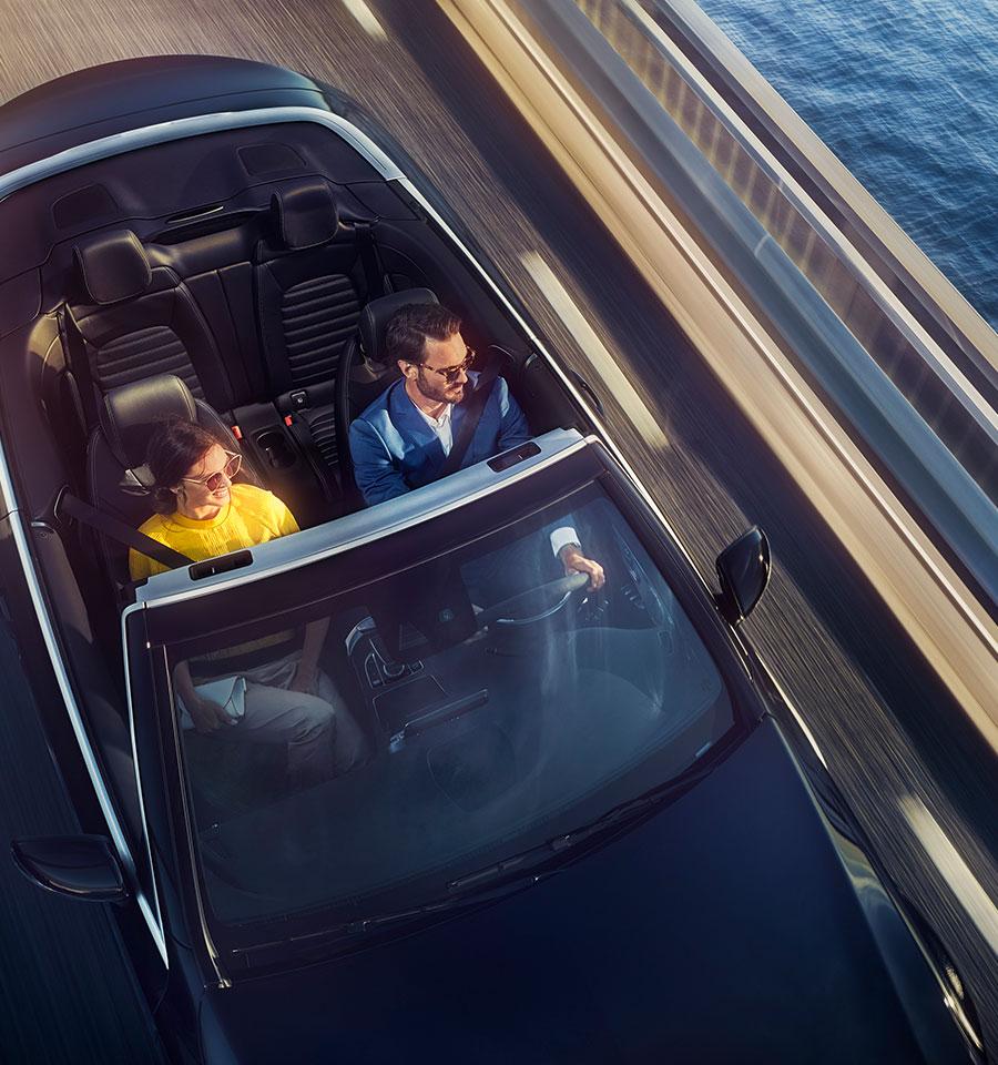 Vogelperspektive auf ein junges Paar, das in einem Mercedes-Benz Cabriolet auf einer Uferstraße fährt.