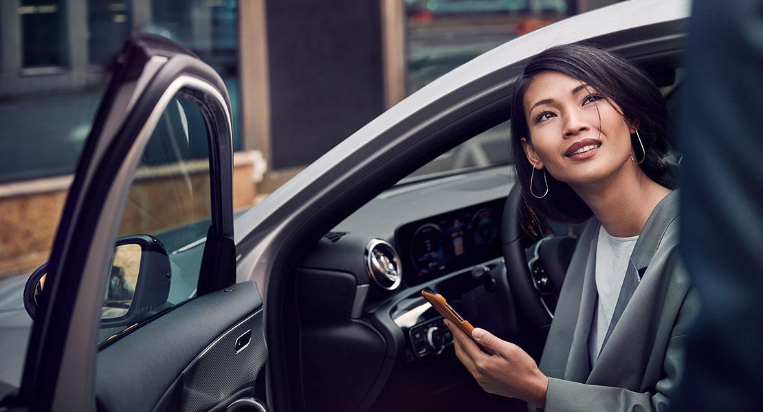 Junge Frau mit Smartphone in der Hand sitzt mit geöffneter Fahrertür in einem Mercedes-Benz
