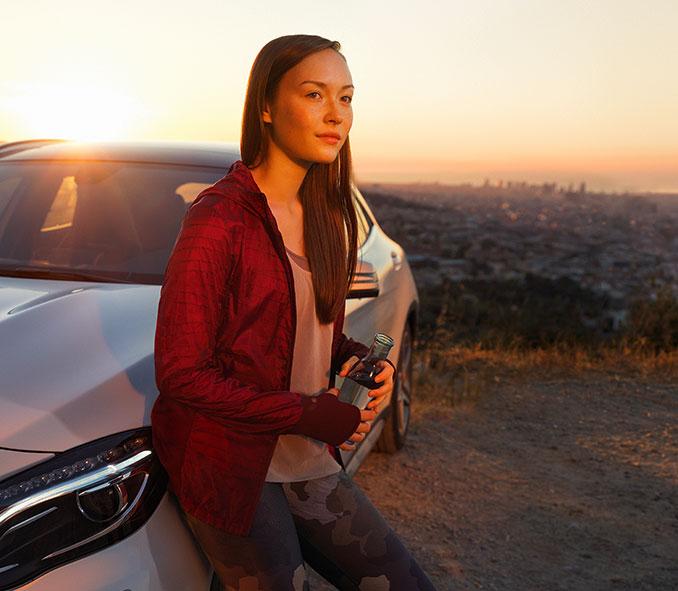 Junge Frau mit Wasserflasche in der Hand lehnt entspannt an einem Mercedes-Benz. Im Hintergund geht die Sonne über einer Stadt unter.