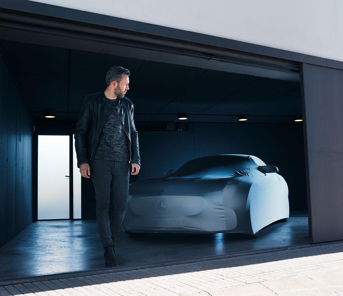 Junger Mann läuft aus einer modernen Garage. Im Hintergrund steht ein Mercedes AMG GT, der mit einer Schutzdecke abgedeckt ist.