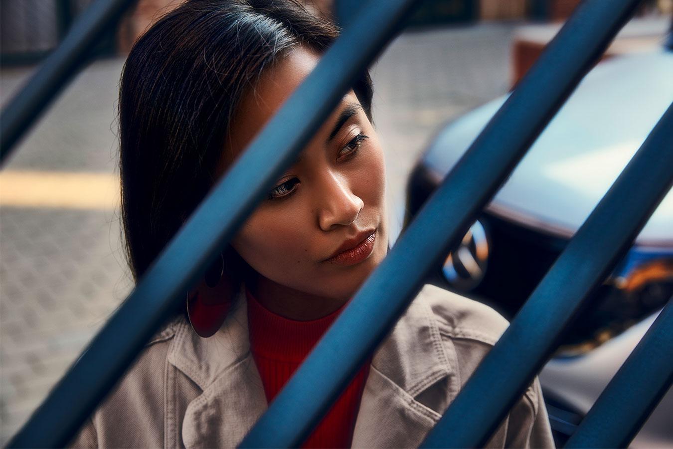 Eine junge Frau sieht durch ein Geländer. Im Hintergrund steht ein Mercedes.
