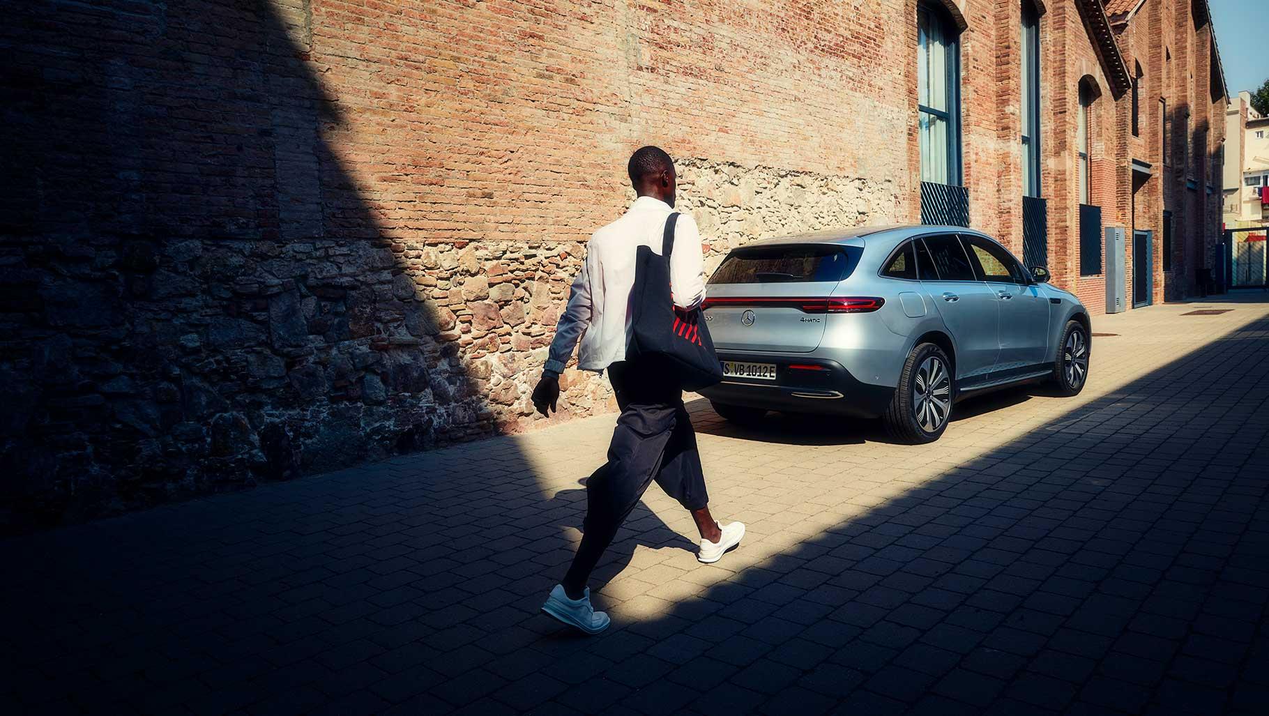 Ein junger Mann läuft an einer Häuserwand entlang, auf einen Mercedes zu.