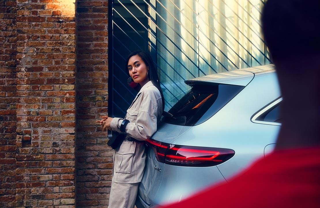 Frau lehnt lässig am Heck eines Mercedes-Benz
