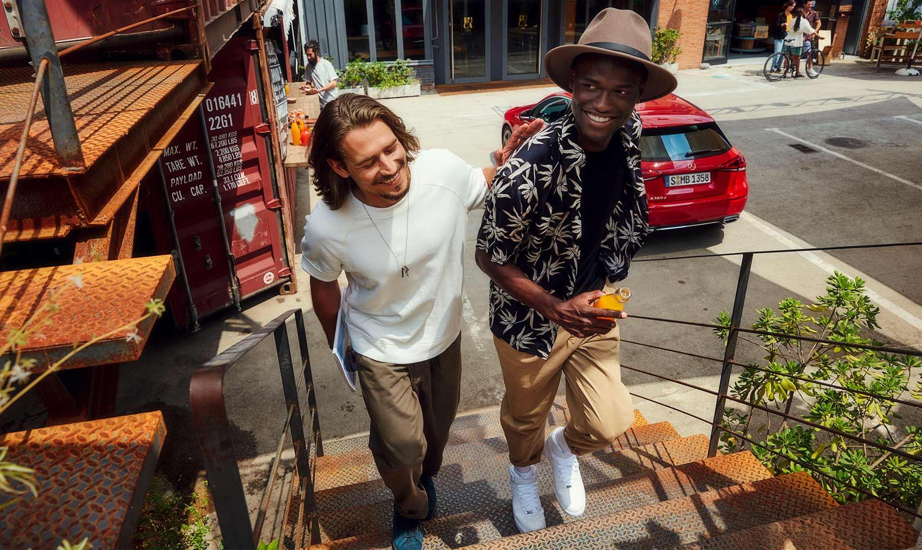 Zwei lächelnde Männer auf einer Treppe mit eine Mercedes-Benz im Hintergrund