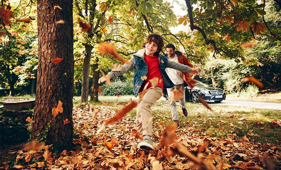 Kind spielt mit seinem Vater im Blätterhaufen im Hintergrund ein Mercedes-Benz