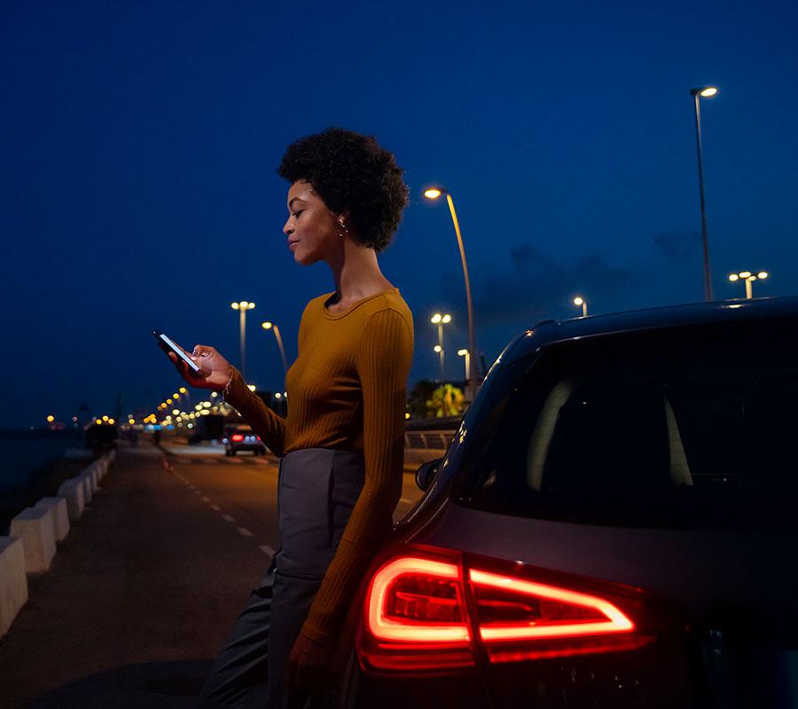 Frau lehnt lässig mit einem Handy in der Hand an ihrem Mercedes-Benz auf einer nächtlichen Straße