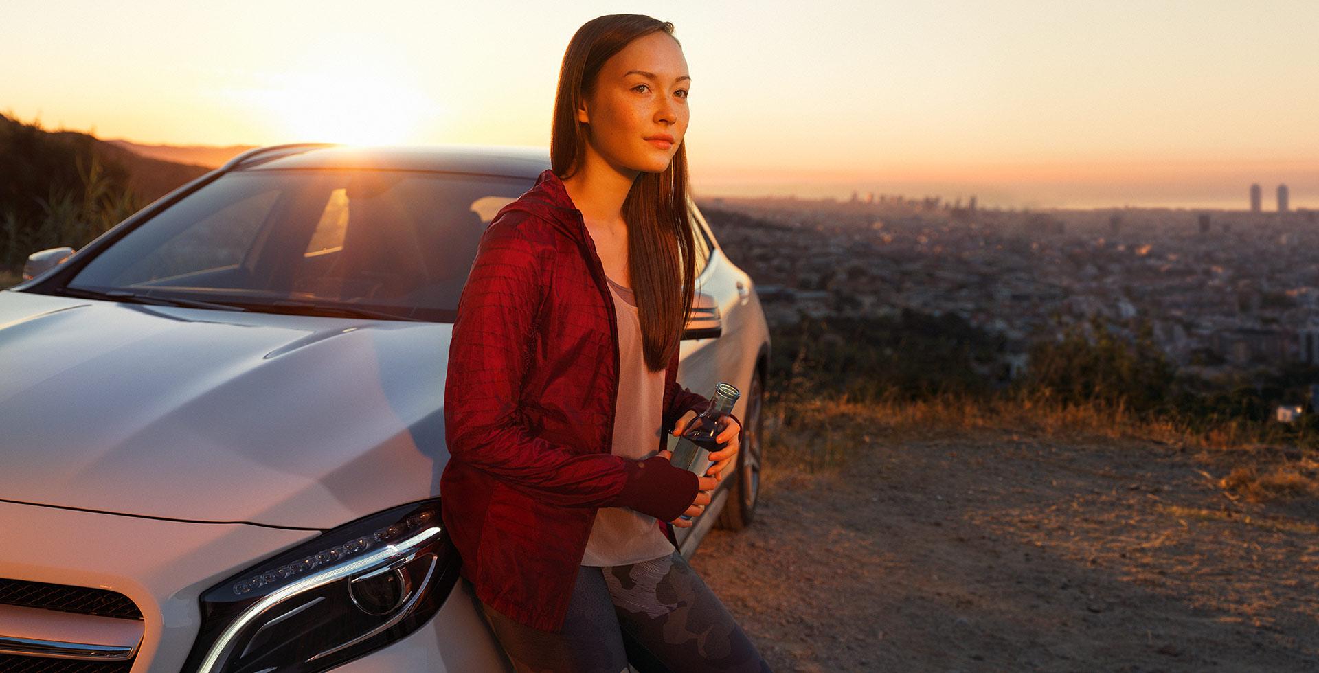 Foto aus dem Bilderpool für Mercedes-Benz Global Service & Parts, auf dem eine Frau entspannt mit einer Flasche Wasser in der Hand an einem Mercedes lehnt.