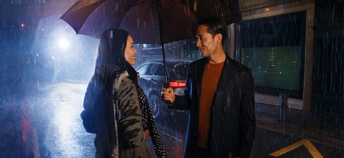 Eine junge Frau und ein junger Mann stehen im Regen unter einem Schirm vor einem Mercedes.