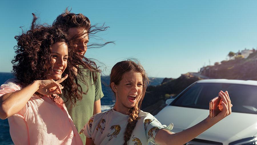 Eine Familie macht am Meer ein Selfie vor einem Mercedes.