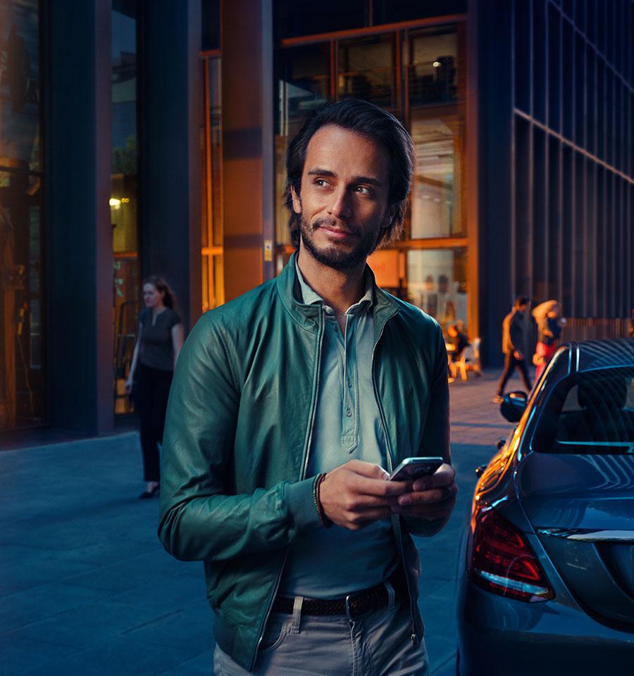 Ein Mercedes-Benz Fahrer steht mit dem Smartphone in der Hand vor seinem Fahrzeug.