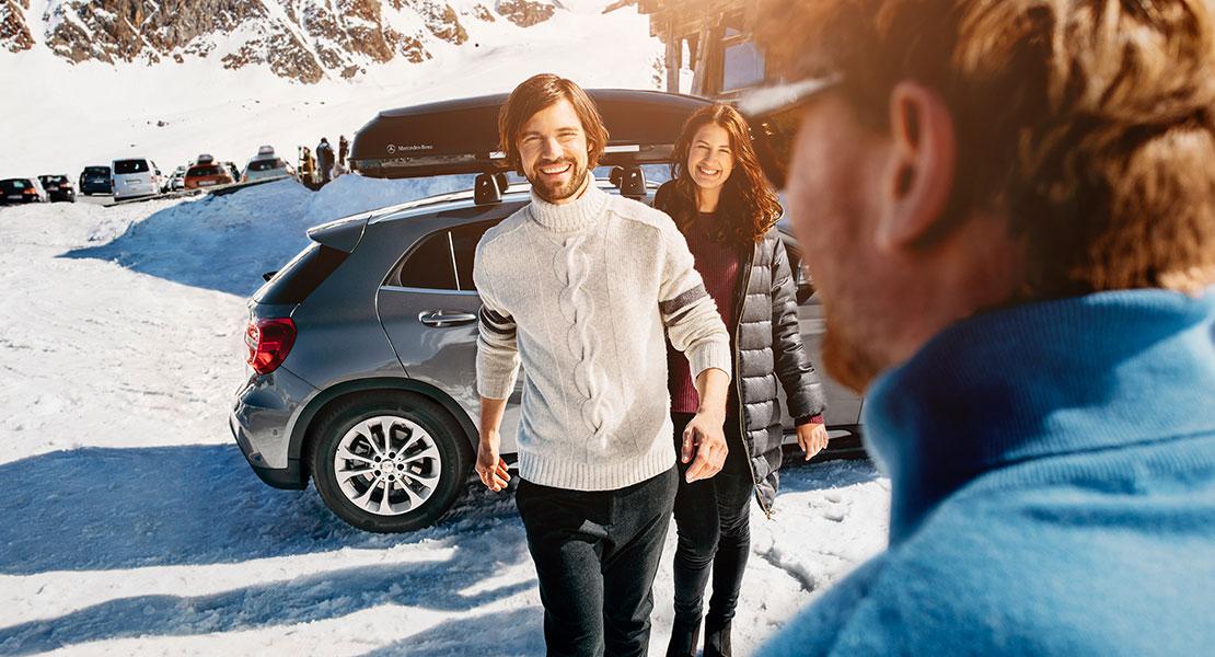 Junge Leute im Skigebiet vor einem Mercedes mit Dachträger.