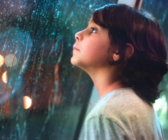 Szene aus dem Film, in der das Kind traurig in den Regen schaut.