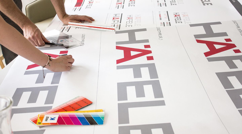 Designer prüfen ausgedruckte Häfele Schriftzüge mit Lineal und HKS Farbfächer.