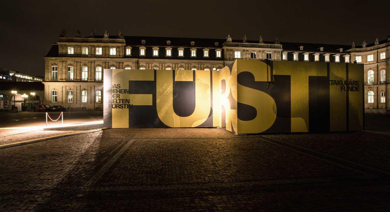 Ansicht der Event-Container der Keltenausstellung von außen auf dem Schlossplatz in Stuttgart bei Nacht.