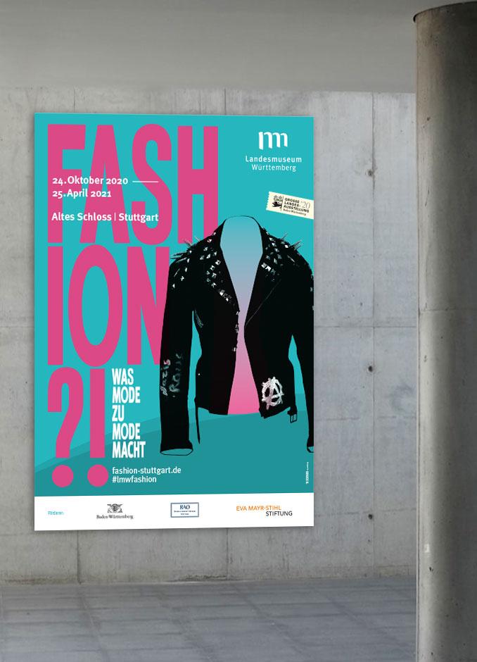 Großes, blaues Fashion?!-Plakat hängt an einer Beton-Wand