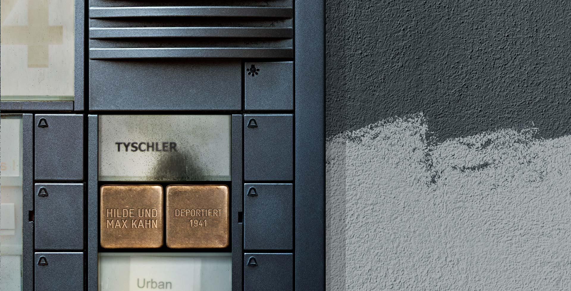 Key Visual zu 'Familienabend': Ein Türklingel, in die Stolpersteine integriert sind.