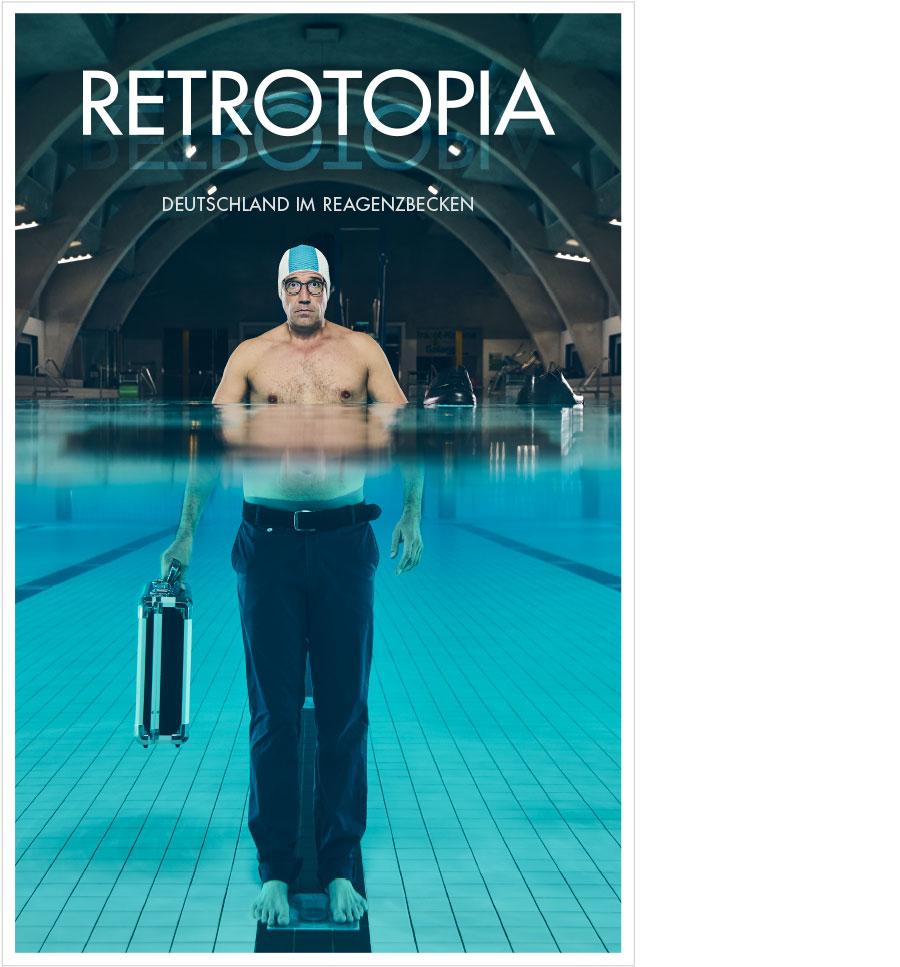 Key Visual zu 'Retrotopia': Ein Mann mit Badekappe, freiem Oberkörper, Anzughose und Koffer steht im Becken eines Hallenbads.