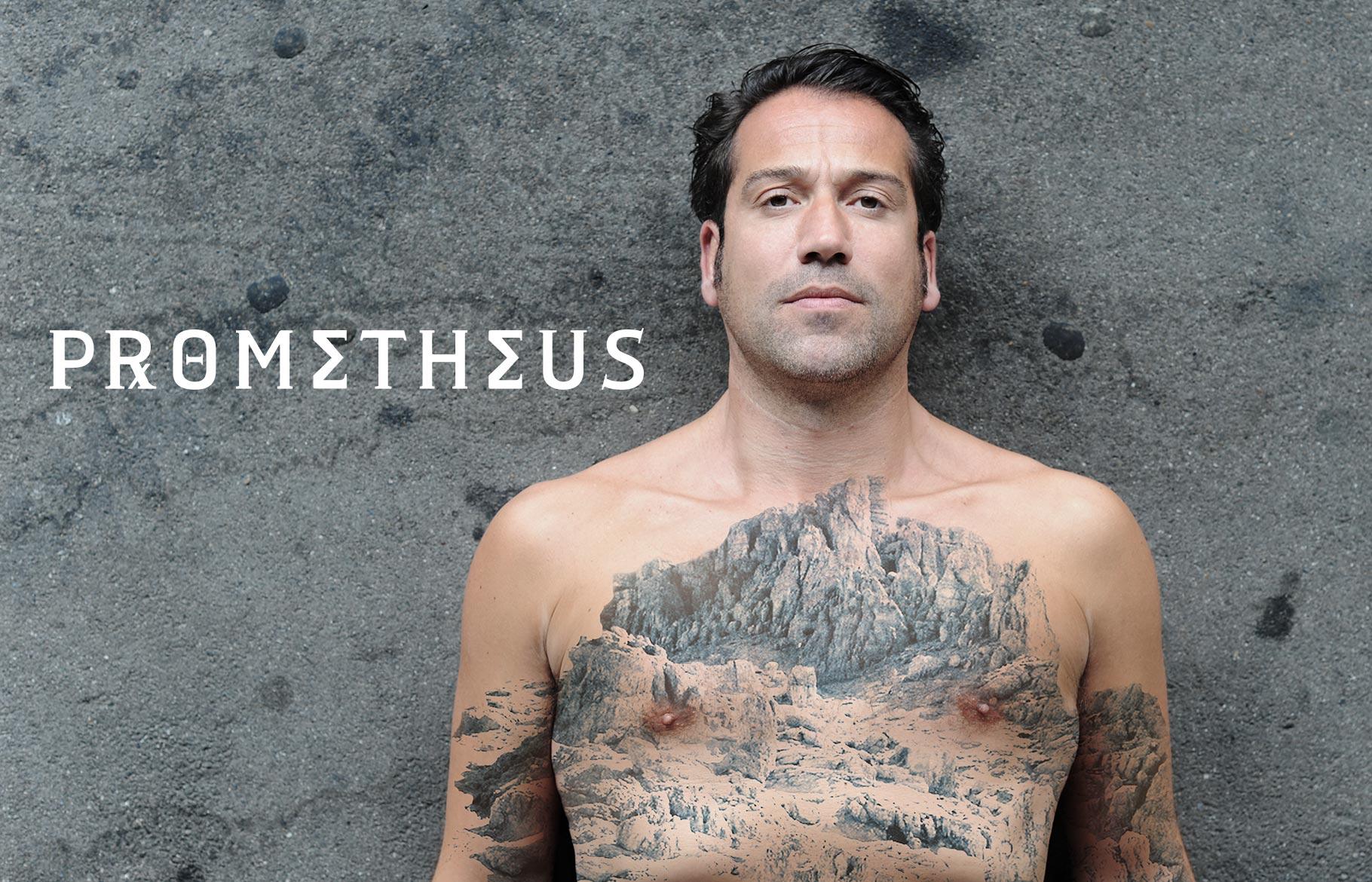 Foto für 'Prometheus': Ein Mann liegt auf dem Asphalt. Auf seinem nackten Oberkörper ist ein großflächiges Tattoo einer Landschaft zu sehen.