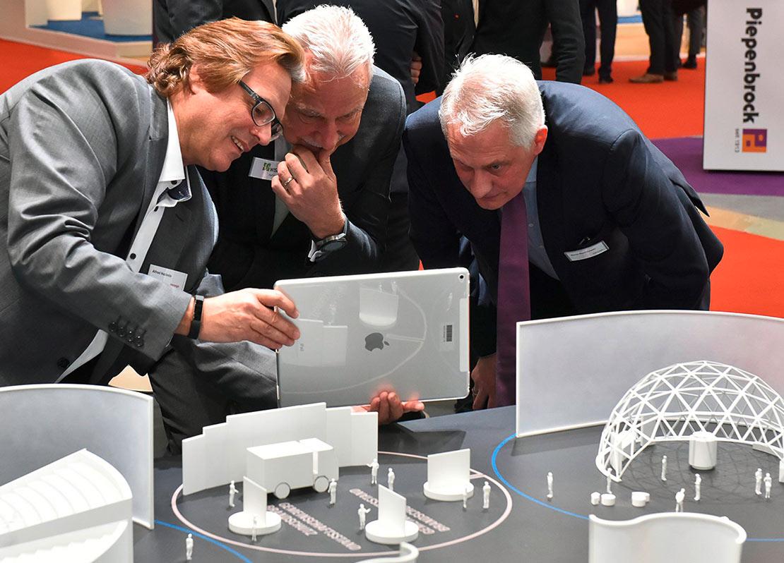 Messebesucher und Mitarbeiter stehen mit einem iPad vor dem Miniaturmodell und nutzen eine Anwendung.
